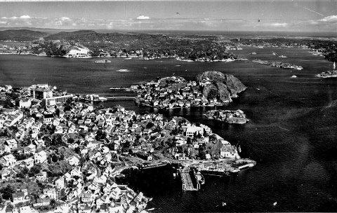 Smedsbukta og Skrubben 1961: Dette er Kragerø for 55 år siden. Lokalsamfunnet er i vekst, og Kragerø Slipp og Mekaniske verksted er i full virksomhet. På Feierheia kan man se at den nye ungdomsskolen under bygging. Det er drift ved Jernstøperiet på Gunnarsholmen. Naper Boktrykkeri var et av landets ledene i sin bransje. 60-årene var en tid der optimismen rådet.