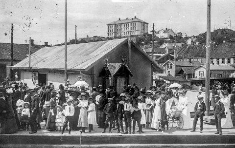 På Dampskipsbrygga rundt 1920: Før jernbanen ble lagt til Kragerø (før 1927) var Dampskipsbrygga stedet hvor det meste skjedde. Det var her folk møtte opp når de skulle reise eller ta imot besøk. Det var til Dampskipsbrygga varer fra den store verden kom til denne lille småbyen. Det var en daglig begivenhet når kystruta, eller postbåten som folk sa, ankom byen, enten fra hovedstaden i øst eller fra vest. Bildet er trolig tatt i forbindelse med et spesielt besøk som ankom byen, da mange har møtt opp i finstasen.