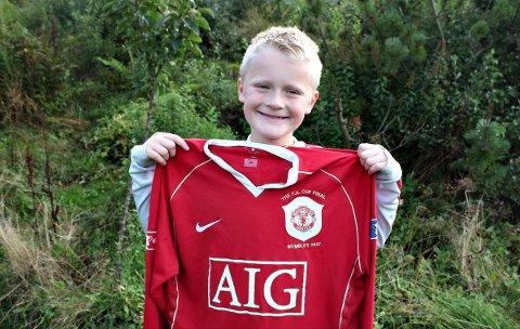 Lars (8) har Manchester United-manager Ole Gunnar Solskjær som fadder, og er med på å gi bort cupfinaledrakta fra 2007 til et godt formål.