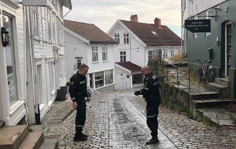 To politibetjenter parkerte bilen ved Tvedestrandsposten og gikk i retning havna.