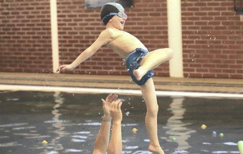 Kjempegøy: Her har svømmelærer Jonas Grønnern akkurat kastet et av barna opp i lufta. Det er ingen tvil om at det er noe barna synes er kjempegøy.