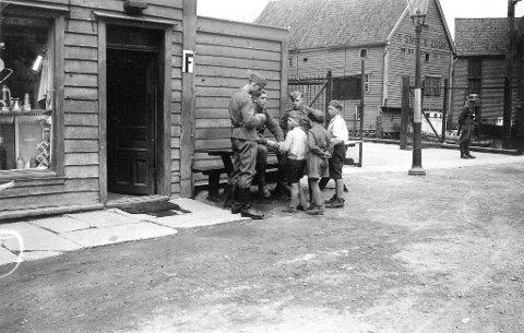 Tyske soldater sammen med nysgjerrige kjuagutter ved                                            inngangen til sjøflyhavnen i Sandviken i 1940. Bildet er tatt av en ukjent fotograf og er fra forfatter Vegard Toskas egen samling.