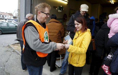 Penger til hjelp: Svein Magne Skeie i Norsk Folkehjelp er glad for alle kronene som kan brukes til å hjelpe. Monica Vikse bidrar gjerne, og er åpenbart fornøyd med å sikre seg en lokalhistorisk bok hun fant på loppemarkedet. – Alle pengene går til å hjelpe folk her lokalt, sier Skeie.