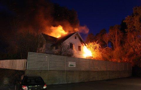 FLAMMER: Flammene slår ut av huset.
