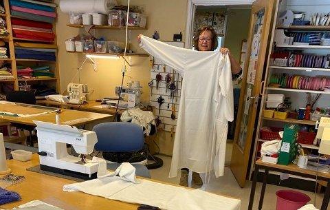 De tre ansatte på Marihøna kan sy opptil 10 slike stellefrakker på en dag. De tåler vask på 90 grader. Her viser aktivitør Hilde Skogvang en ferdigsydd frakk.