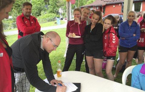 SIGNERTE: Samuel Ivar Arnason signerte kontrakten som hovedtrener for RHH med sportslig leder Hallgeir Bakken og styreleder Marianne Røgeberg som vitner i tillegg til flere av spillerne i klubben.