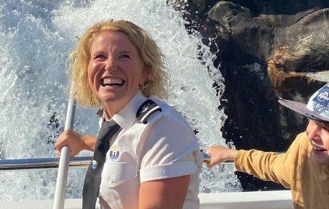UNGDOMSKJELDE: Helene Helgøy fangar litt vatn til passasjerane sine frå ungdomskjelda i Lingvongfossen på eitt av fjordcruisa til Helgøy Skyssbåt i sommar.