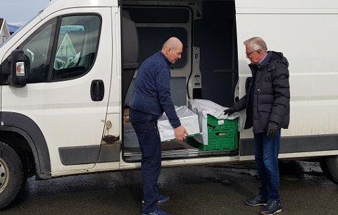 Georg Søyseth (til venstre) fikk med seg hyttenaboer i Trondheim til å kjøpe påskevarer på nærbutikken på Veiholmen. Mandag kom varene til Trondheim, og Søyseth kjørte dem ut. Her leverer han til Ole Johansen, som også har landsted på Veiholmen.