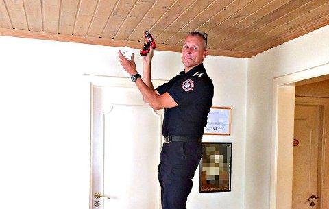 HJALP TIL: Her setter branninspektør Rune Huse opp en røkvarsler hjemme hos en dame i 90-årene.