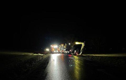 Tungbilberger holdt mandag kveld på å hjelpe lastebilen opp fra grøfta. Både bilen og hengeren står utenfor vegen, som er delvis sperret.