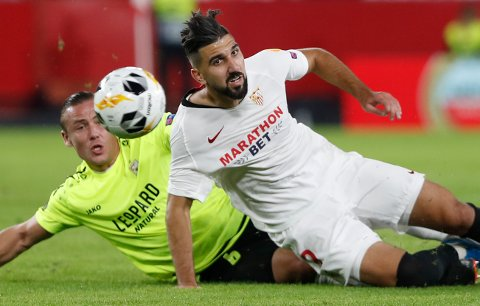 Sevilla's Munas Dabbur, right, fights for the ball with Dudelange's Tom Schnell during the Europa League group A soccer match between Sevilla and Dudelange at the Estadio Ramon Sanchez-Pizjuan stadium in Seville, Spain, Thursday, Oct. 24, 2019. (AP Photo/Miguel Morenatti)