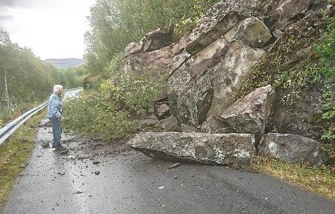 STEINRAS: Det har rast ut store steinblokker som sperrer veien inn til Sildvik. På bildet ser vi Monart Heiberg som betrakter steinblokkene som har rast ut.