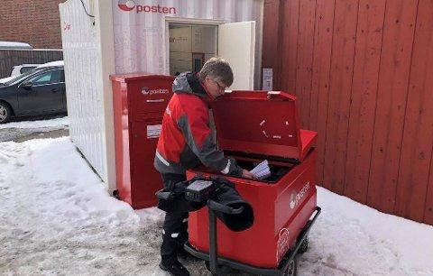 Postbud Svein Kyrre Hamnes med dagens leveranse av pakker og brev til postautomaten i borettslaget.