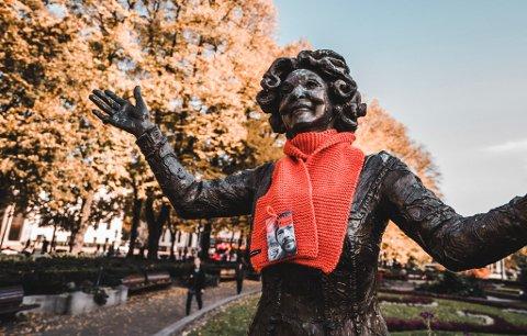 STRIKKEDUGNAD: Oransje skjerf er Kirkens Bymisjons årlige strikkedugnad og aksjon for et varmere samfunn. I år får de drahjelp av TV-aksjonen. Her er det statuen av Wenche Foss som har fått et varmende skjerf. Pressefoto: Kirkens Bymisjon