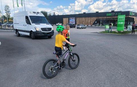 SKUMMELT: Flere skoleelever må krysse utkjøringen fra butikkene på Hanstad til og fra skolen. Det skaper bekymring. Her passerer Hadrian Øverland Berg og Mille Kveseth Nygaard foran en bil.