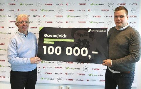 100.000 kroner: Finn-Roald Schie får overrekt gavesjekken fra daglig leder på Energiverkets Østfold-avdeling, Glenn Pettersen. Foto: Energiverket