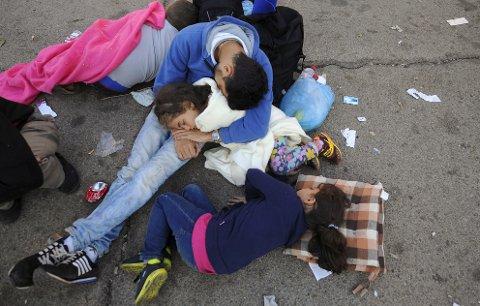 Flyktninger fra Syria sover på bakken ved togstasjonen i Gevgelija etter at de, sammen med hundrevis av andre flyktninger, har kommet fram til Makedonia i dag søndag.