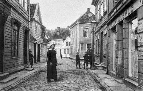 På dette fotoet frå 1915 kan ein sjå eit av byens mange mjølkeutsal I Nøstegaten. Her var det mjølk frå Askøy som blei solgt over disk. På skilta utanfor utsalet står det at dei også har egg og kaker, samt rømmekolle til sals her. Før i tida myldra det av slike små utsal rundt om i byen.