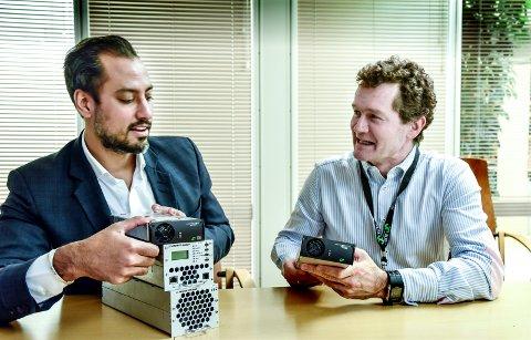 ELTEK: Omformeren som markedsdirektør i Eltek Morten Schøyen (til høyre) holder i hånden, erstatter de tre omformerne og likeretterne som innovasjonsdirektør Satvir Singh Parmar har. Eltek er den første produsenten innen strømforsyning som har klart å forene disse tre produktene.