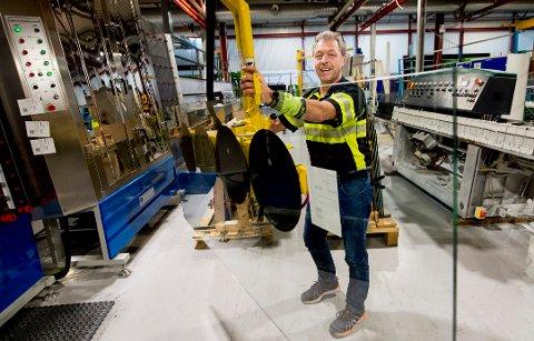 Leif Hansen polerer de skarpe kantene på glasset med en av de poleringsmaskinene. De tunge glassene blir løftet med vakum i en kran.