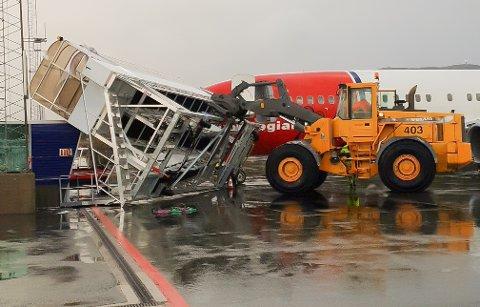 Den spesialbygde gangbrua, som skal gjøre det enklere for passasjerene å komme seg om bord i flyet, tippet i de sterke vindkastene på Evenes søndag.