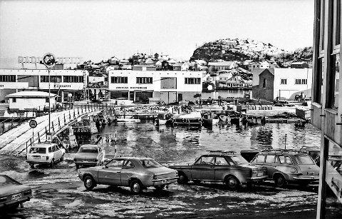 Jens Lauersøns plass på 1970-tallet: Bildet kan fortelle mye om de store forandringene som har skjedd i dette området. På brygga har fiskehandlerne Krafft og Marthinsen satt opp sine nye fiskehaller. Den gang var det åpning mellom byggene og ut til Dampskips- og fiskebrygga. Legg også merke til det enormt store reklamen til «Radionette» på taket til E.J. Kraffts butikk.