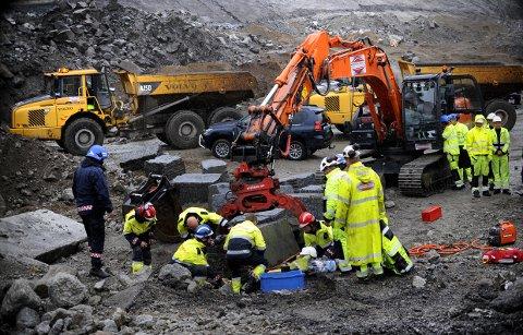 Mannskaper fra Brann og redning samarbeider med anleggsarbeiderne for å få den forulykkede løs