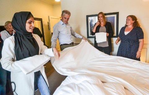 FIKK OPPLÆRING: Zarah Tajik (t.v.) og Frida Skaanes forklarer Jonas Gahr Støre hvordan han skal gjøre i stand ei hotellseng. Til høyre Hilde Hoff Håkonsen.