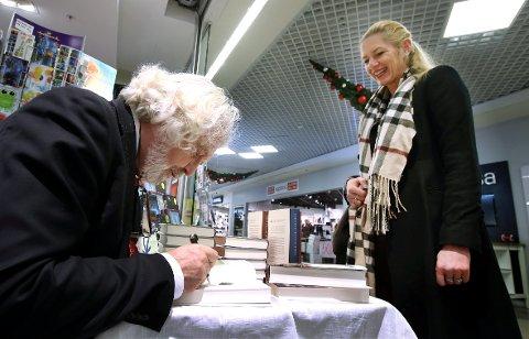 SKRIVER UNDER: Anne Grønlie (49) fra Ånnerud sikrer seg tre signerte bøker fra Edvard Hoem. – Han ligner på nissen, det er lett å få julestemning. Hyggelig at en forfatter besøker oss i julestria, sier hun.