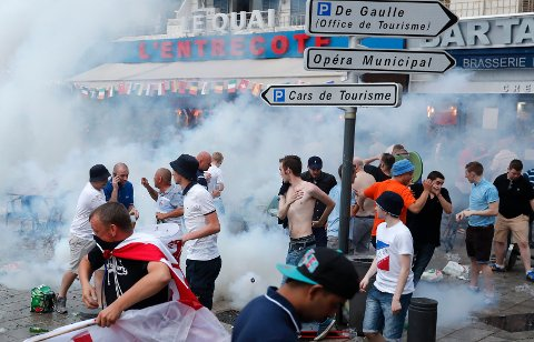 England supporters take evasive action after French police fired tear gas at them in downtown Marseille, France, Friday, June 10, 2016.  Some minor scuffles on Friday and the brief clashes late Thursday revived bitter memories of days of bloody fighting in this Mediterranean port city between England hooligans, Tunisia fans and locals of North African origin during the World Cup in 1998, and raised fears of more violence ahead of Saturday's European Championship match between England and Russia at the Stade Velodrome.(AP Photo/Darko Bandic)