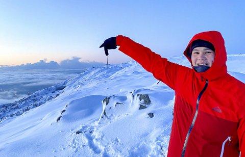 App-utvikler Ivan Hjelmeland peker på Ulriksmasten, som ligger 45 minutters gange fra Haukelandsstikkene hvor han her befinner seg i flott vintervær.