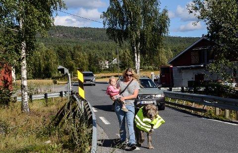 TRANGT: – Det er nå så mye trafikk i Eidalsveien at jeg så langt det er mulig unngår å gå etter veien, sier Anita Jahr Ask. Her sammen med datteren Saga (1 1/2) og hunden Ulv, mens de viser hvor smal veien er rett ved huset deres.