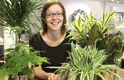 Eldbjørg Midtbø Steindal på Rognaldsen Gartneri viser fram eit vell av grøne planter som yucca (i midten til høgre), dracena (bak høgre og venstre) og grønnrenne (framst til høgre) for å beskrive haust-trendane i sin bransje. Foto: Liv Standal