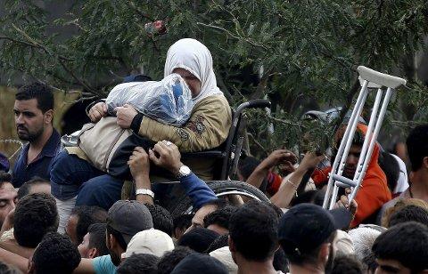 Flyktningestrøm: En handikappet syrisk kvinne gråter andre flyktninger. Bildet er fra grensen mellom Makedonia og Hellas lørdag.