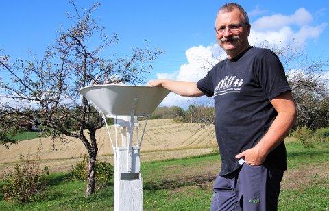 LANG TRADISJON: Hans Erik Flatla ved nedbørsmåleren som har stått på gården på Kalvsjø i 122 år.
