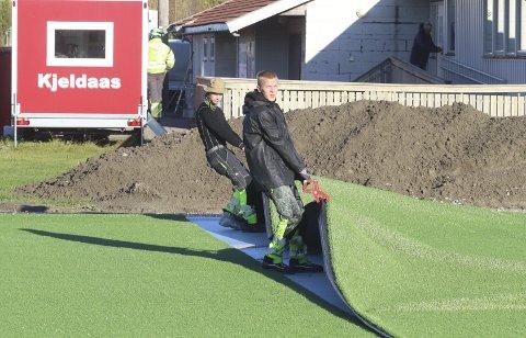 Strekker duken: Denne uken har et arbeidslag lagt kunstgresset på den nye fotballbanen. Foto: Pål Nordby