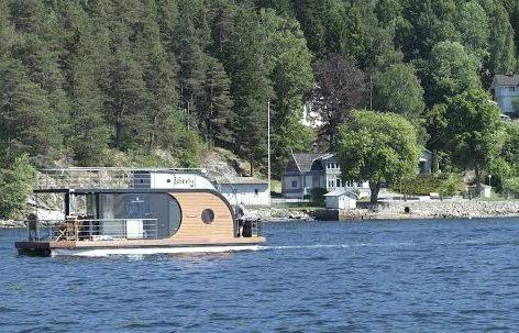 UVANLIG FARKOST: Her er husbåten Liberty fotografert fra en annen båt mens den passerer Uranienborg, Roald Amundsens hjem på Svartskog. Nina Andresen står bak roret, ektemannen John Vinneng står bak og fisker mens datteren sover på dekk. FOTO: PER JOHANSEN