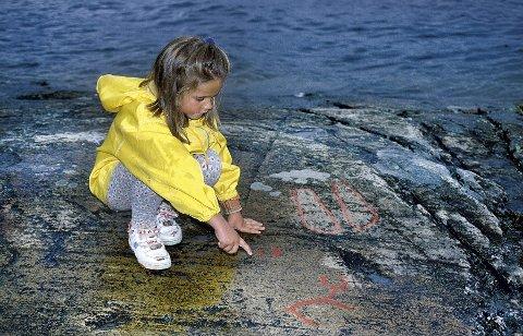 Helleristninger: Leyla Østerbø har satt seg ned ved Romerikes eneste helleristninger, som ligger like ved badeplassen ved Bingsfossen. Disse kan være nær 4.000 år gamle.