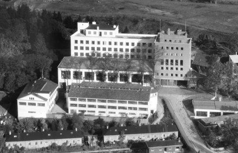 På dette flyfotoet ser ein godt den kombinerte fabrikkbygningen Sverre Munck fekk reist i 1946. Til høgre ser ein direktørbustaden på toppen. Til venstre på den store takterrassen står huset Sverre Munck fekk bygd til huslegen sin.