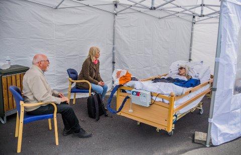 På avstand: Mandag fikk Hans Olav Nøklestad og datteren Kristine besøke kone og mor Randi på Fredrikstad korttidssenter. Men de fikk verken klemme eller komme for nært av hensyn til smittevernet.
