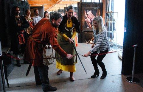 MED SVERD: Høvding Pia Jorde Løvgren i Borre Vikinglag klipper båndet for å markere at utstillingen er åpnet.