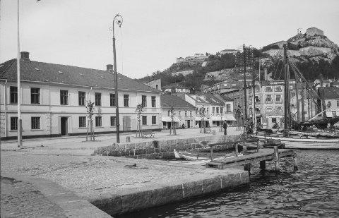 TELEFONSTOLPE: Foto av Indre havn fra første del av 1900-tallet. Merk telefonstolpen til høyre i bildet. Til denne stolpen er det festet nærmere 150 telefonledninger. Ved siden av stolpen ligger det en liten bensinstasjon med skiltet SHELL – BENZIN. FOTO: NASJONALBIBLIOTEKET