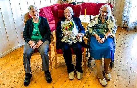 I midten sitter bursdagsbarnet Inga Gustavsen med blomsterbuketten. De to andre som også er 100 år er, Ester Skarvang til venstre og Tordis Johansen til høyre.