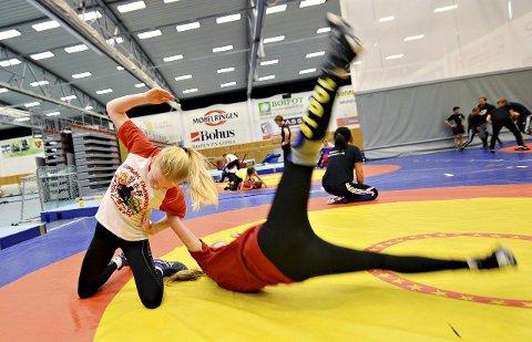 Julie Dalsbotten slenger rundt på brytevenninna Lilly Morken. Jentene har tatt turen fra Kolbotn til Kristiansund for å delta på brytecamp i Braatthallen.