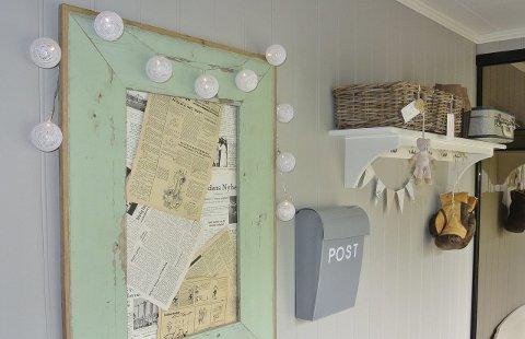 GAMLE AVISER: Ei stor bilderamme laga av røff plank er dekorativt på veggen med gamle avisar inni.