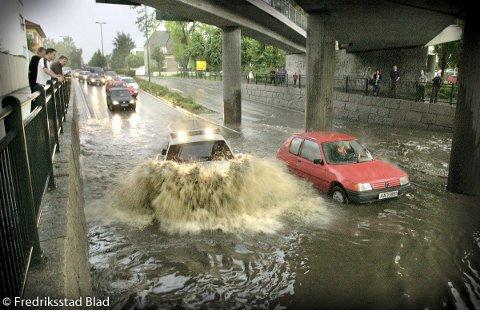 Regnskyll skapte flom flere steder i Fredrikstad: Bilen til høyre stoppet i vannet i undergangen ved St. Croix mens politibilen under utrykning klarer å forsere vannmassene og passere.  Fotograf: Lasse Eriksson TattDato: 20000830