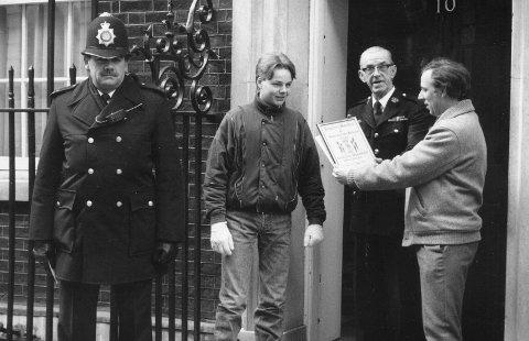 ENDELIG: Bobbyen virket ikke helt komfortabel med situasjonen, men Andrew Kristiansen og Espen Sandaker fikk overlevert diplomet til en tjenestemann i Downing Street No. 10 som tok imot på vegne av statsminister Margaret Thatcher.