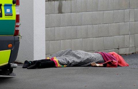 TERROR: Et tildekket lik ligger på fortauet utenfor en av moskeene som ble angrepet fredag.