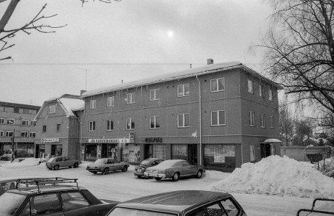Skoleveien 1 i Ås skal bli legesenter. Vinterbilde med parkerte biler utenfor, stor snøhaug. Murbygninger i Ås sentrum.