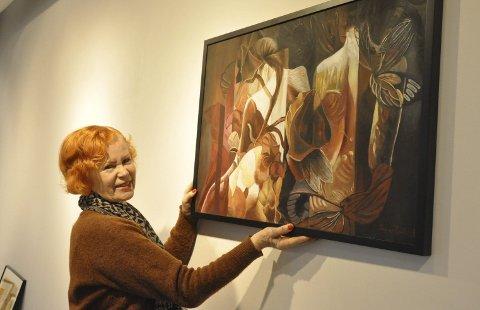 Monterer: Leder i Eidsberg kunstforening, Gro Elnes, i ferd med å henge opp et maleri av Trøgstad-kunstneren Trygve Fjeld.